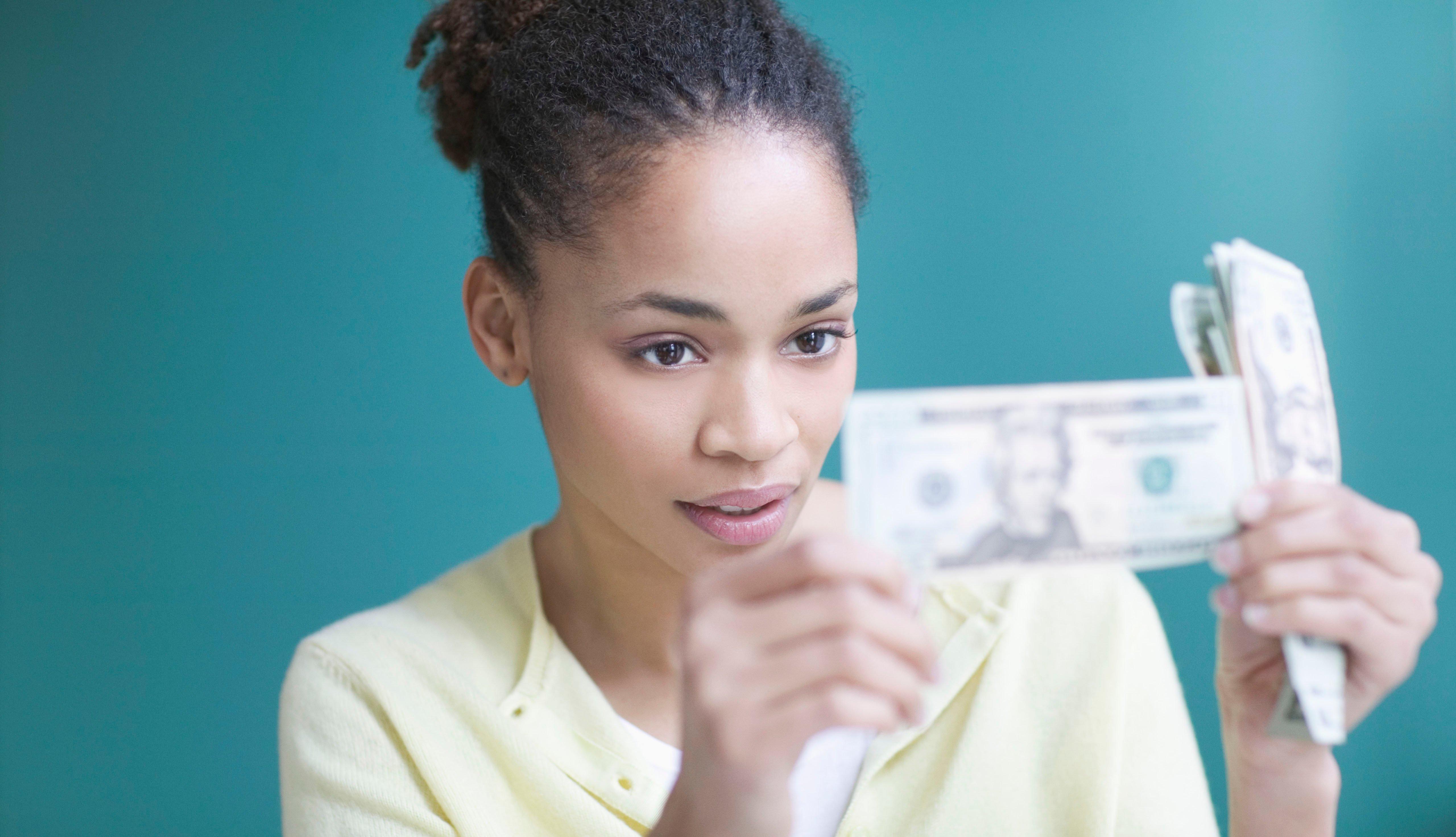 Mujer viendo dólares que sostiene en sus manos