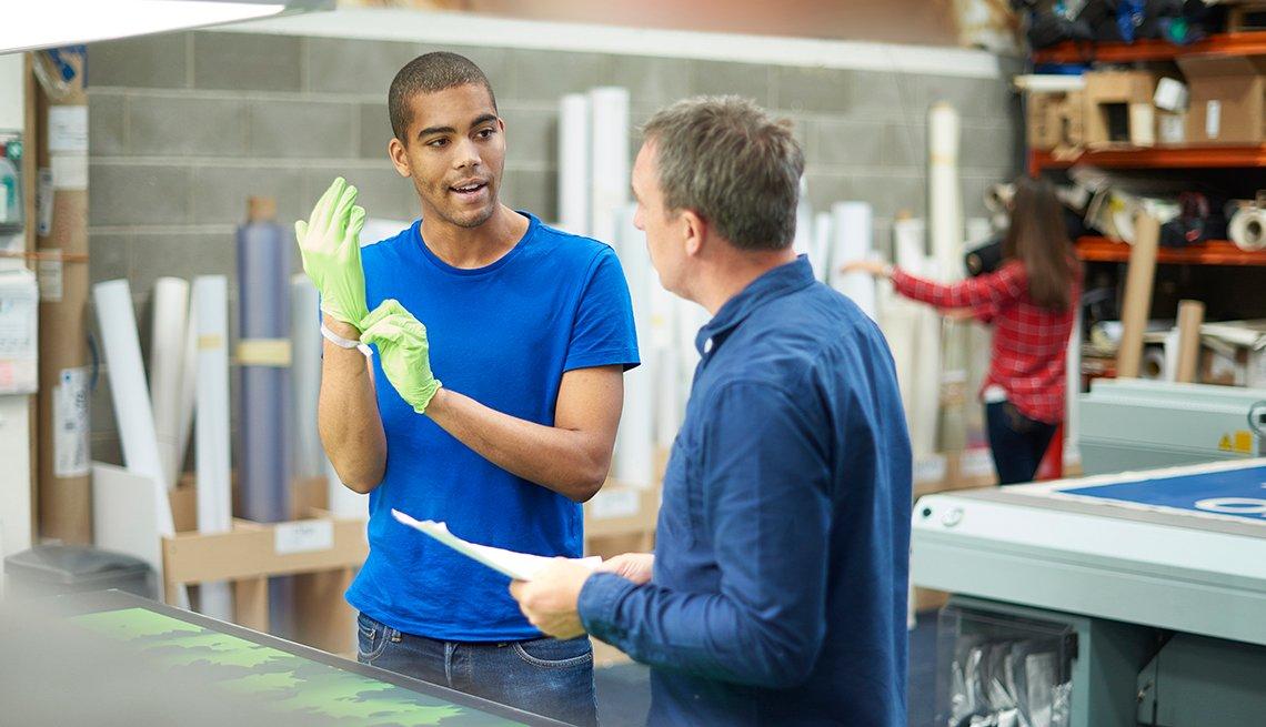 two men talking in a workshop
