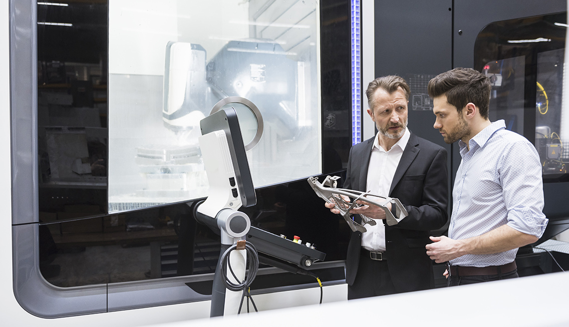 two men talking in front of a robot