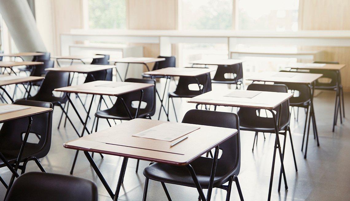 Salón de clases con escritorios y sillas vacías