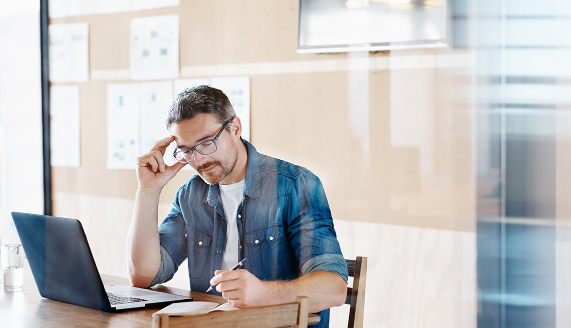 Hombre sentado frente a una computadora personal