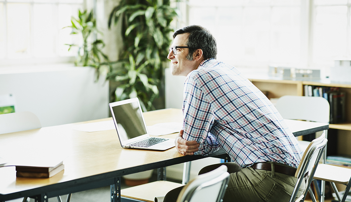 man sitting at a table in front of a computer