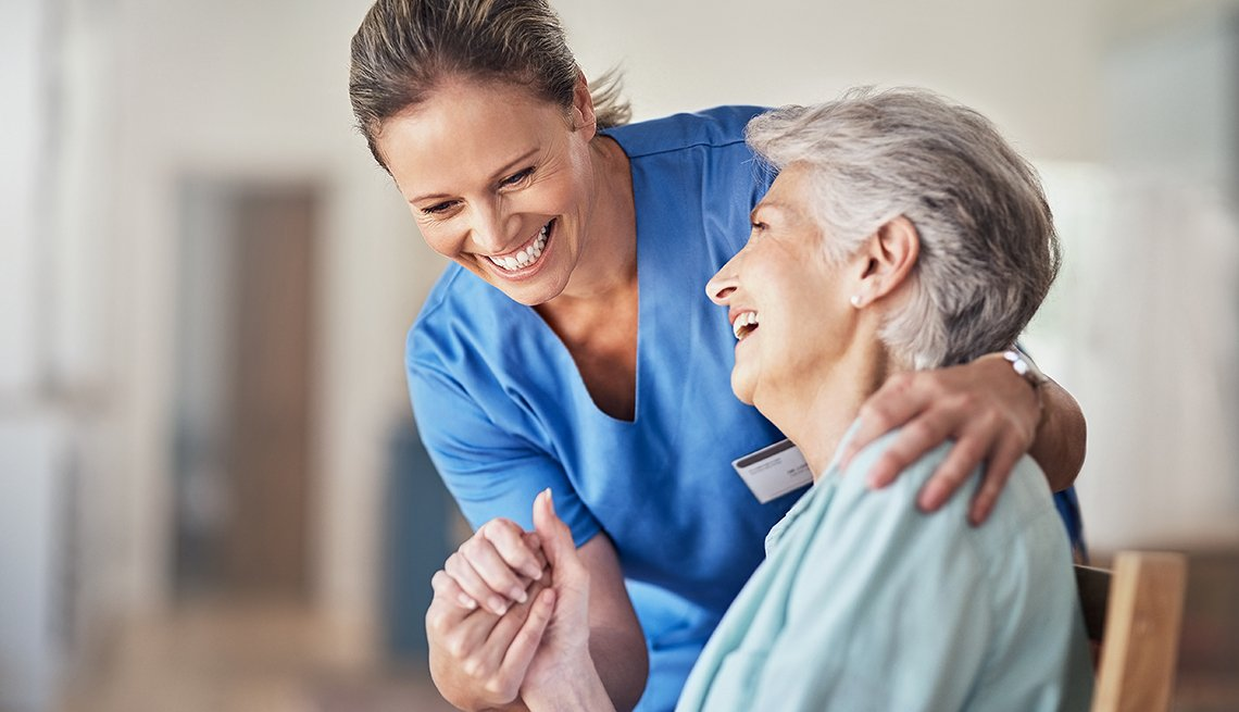 a nurse holds an older woman's hand