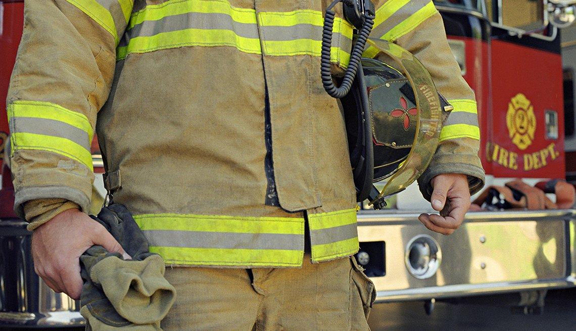 A fire fighter standing next to a fire truck