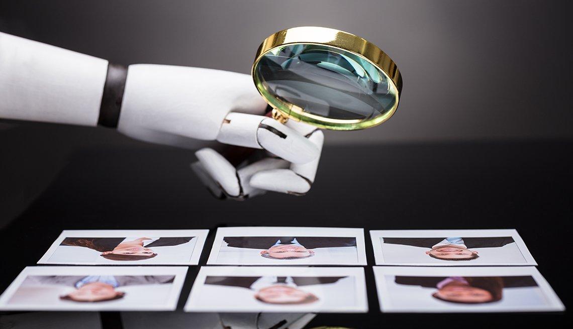 Mano de un robot sosteniendo una lupa sobre varios retratos
