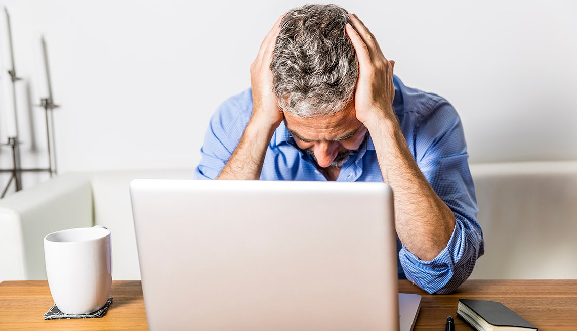 a man in front of a laptop holds his head in his hands