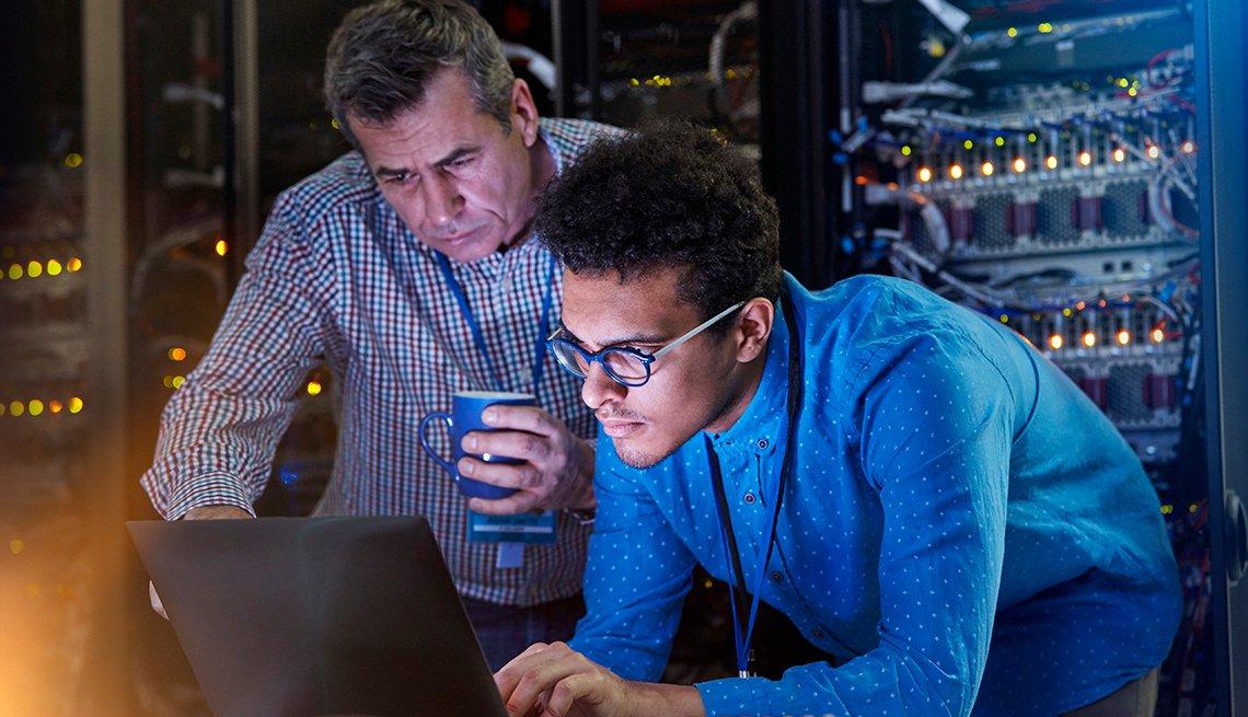 Dos técnicos viendo una computadora en un cuarto de servidores.