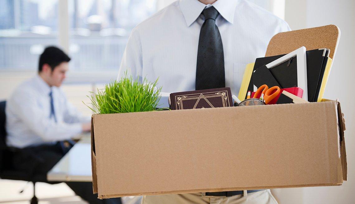 Un hombre sostiene una caja con suministros de oficina