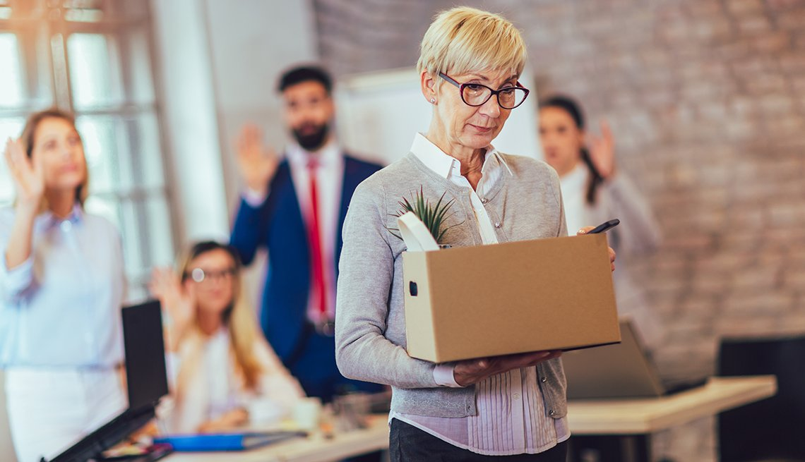 older woman leaving office with a box of belongings
