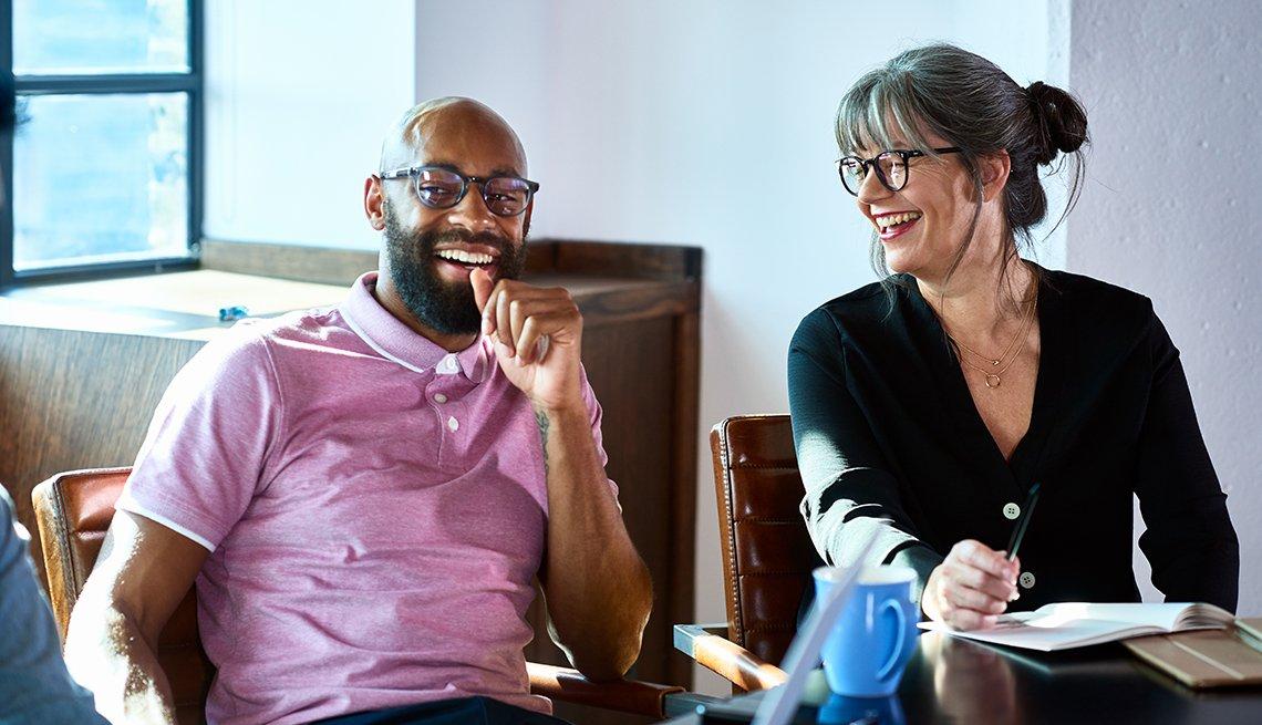 Hombre y mujer riéndose en una oficina