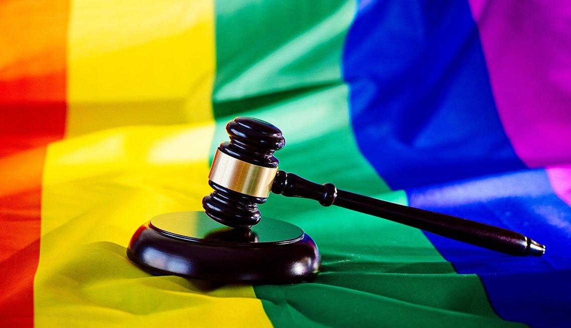 Martillo de madera sobre una bandera con los colores del arco iris