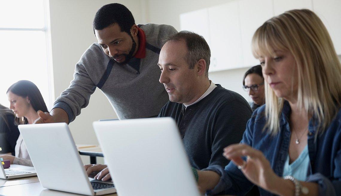 Adultos atienden a una clase de computadores.