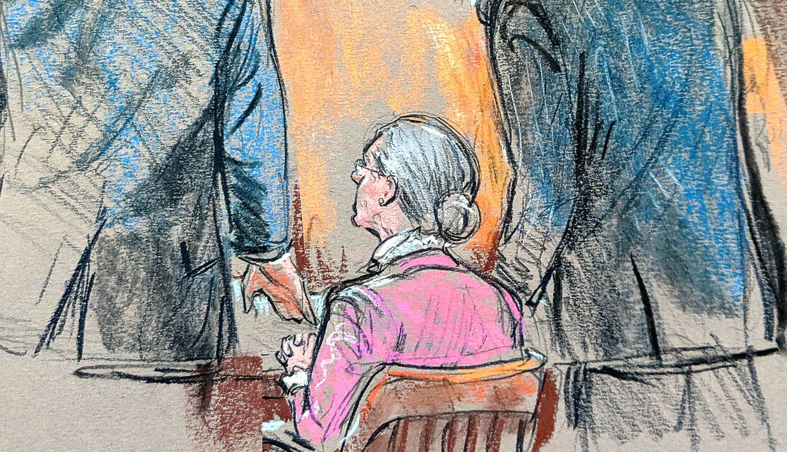 Two lawyers stand next to a woman sitting down wearing a pink sweater
