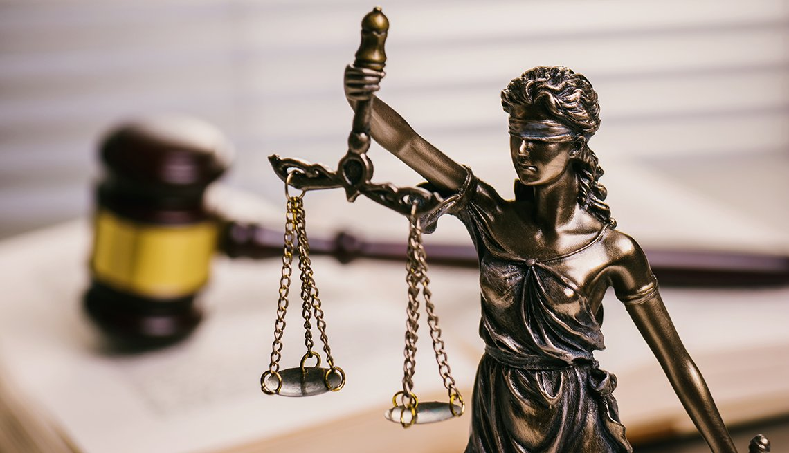 A wooden gavel with the scales of justice statue