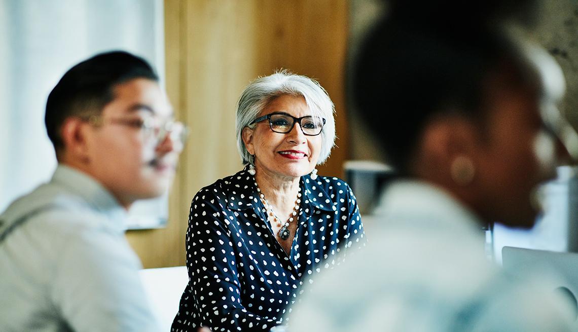 Mujer mayor sentada en una oficina con dos personas más.