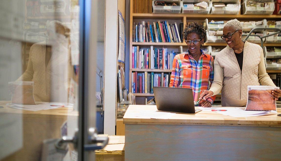 Dos mujeres mayores viendo una computadora portátil en una oficina.