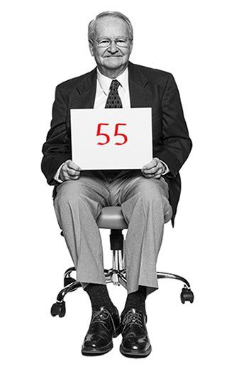Jack Gross holds a placard with the number 55 written on it in red marker sits in an office chair