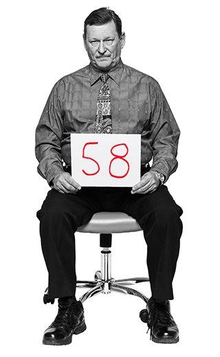 Walter Mikulan, 58, sentado en una silla de oficina sosteniendo en sus manos un letrero con su edad.