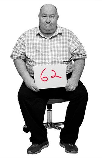 Floyd Cardwell, 62, sentado en una silla de oficina sosteniendo en sus manos un letrero con su edad.