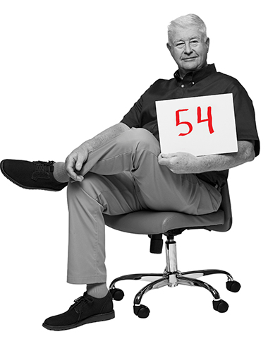 brian reid sits in an office desk chair holding a placard with the number 54 written on it