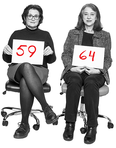 julianne taaffe and kathryn moon are pictured sitting on office chairs holding placards with their ages written on them