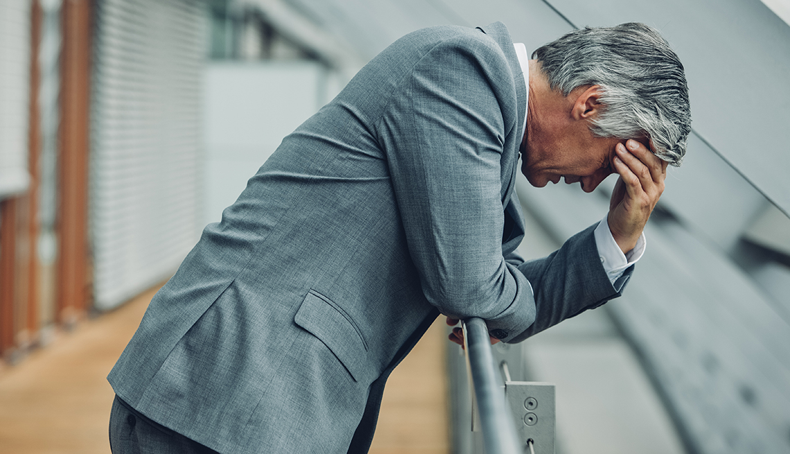 Un hombre mayor deprimido con la cabeza entre las manos