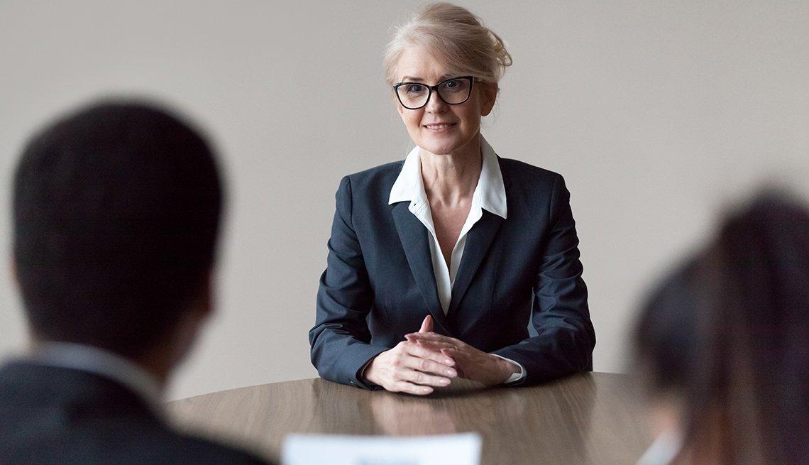 Mujer mayor sonriendo a sus empleados.