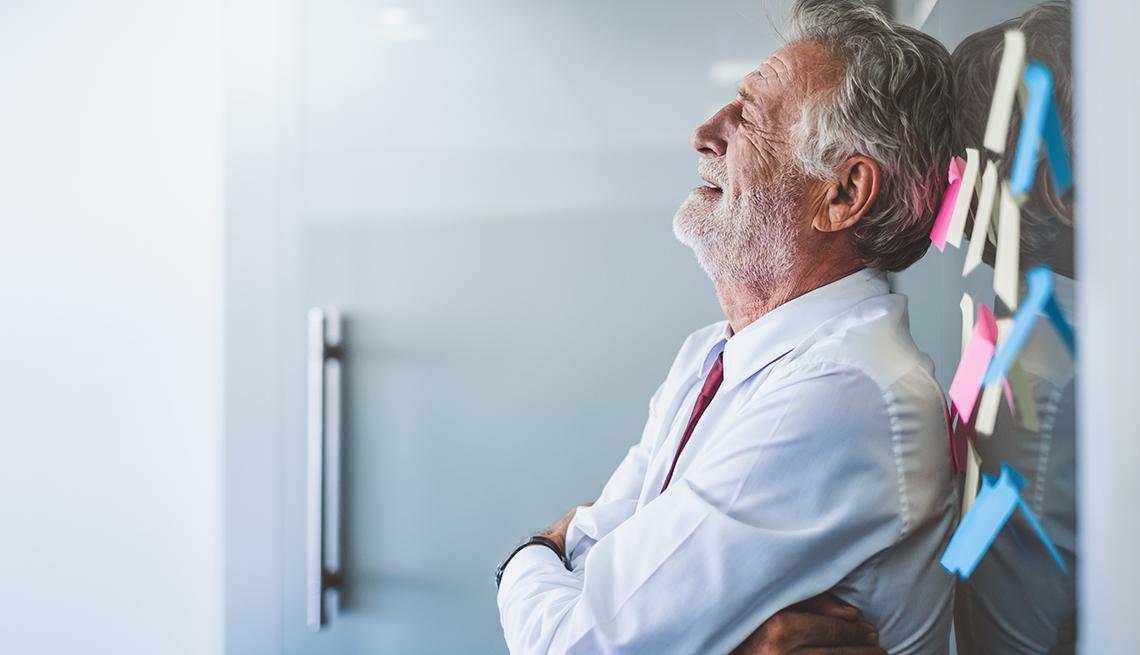 Hombre mayor recostado sobre la pared de una oficina.