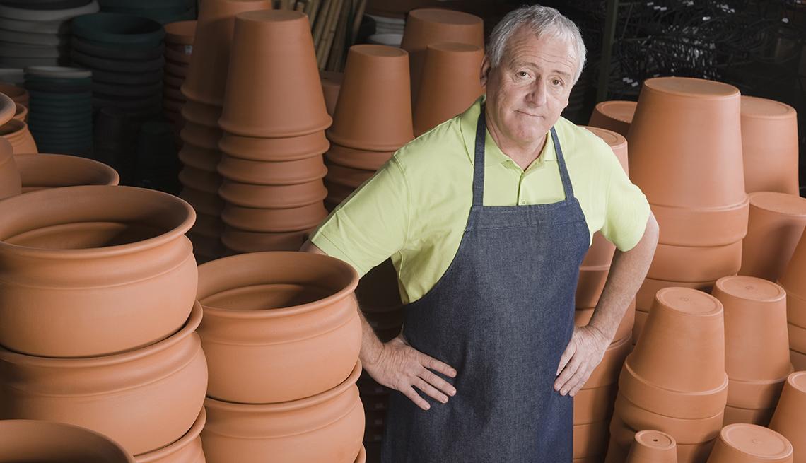 An older man standing next to flower pots