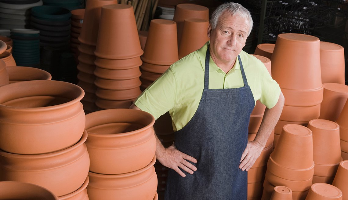 An older man standing next to flower pots