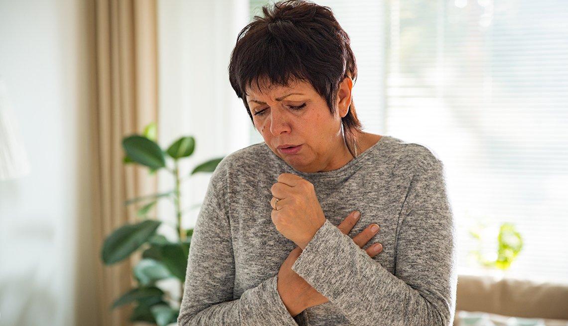 Mujer tosiendo y con los brazos en el pecho.