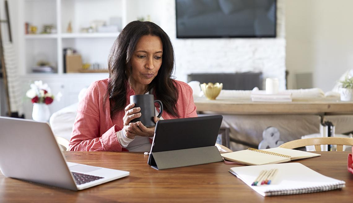 Mujer trabajando en un escritorio desde su casa.