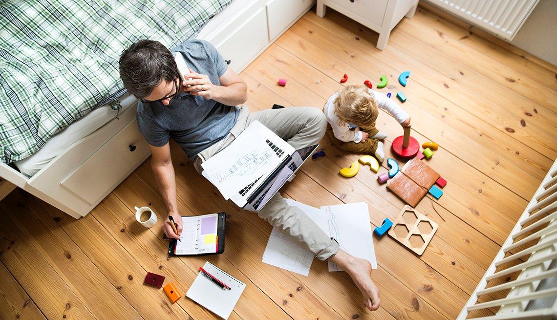 Un hombre trabajando en casa mientras su hijo juega al lado.
