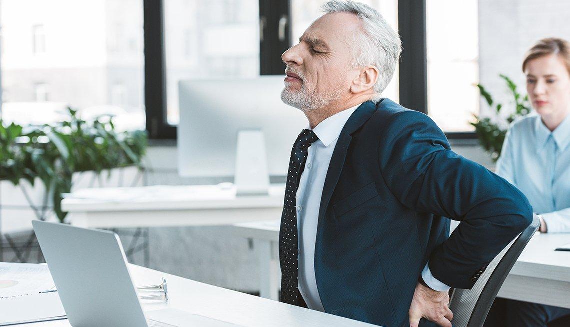 Hombre mayor sentado frente a un escritorio en una oficina que se queja de dolor de espalda.