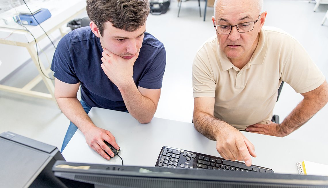 An older male works with a younger male on a computer
