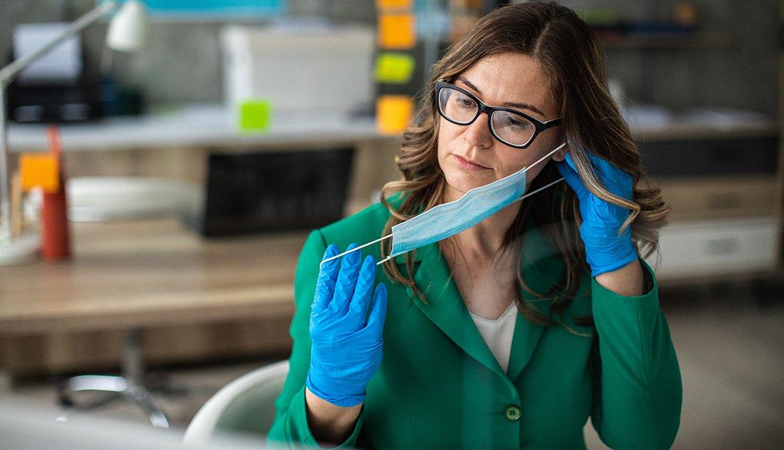 Mujer con guantes en una oficina colocándose un tapabocas.