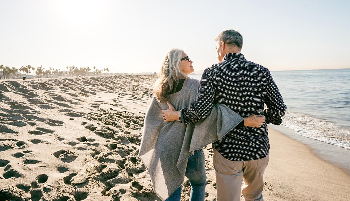 Pareja mayor caminando abrazada por la playa