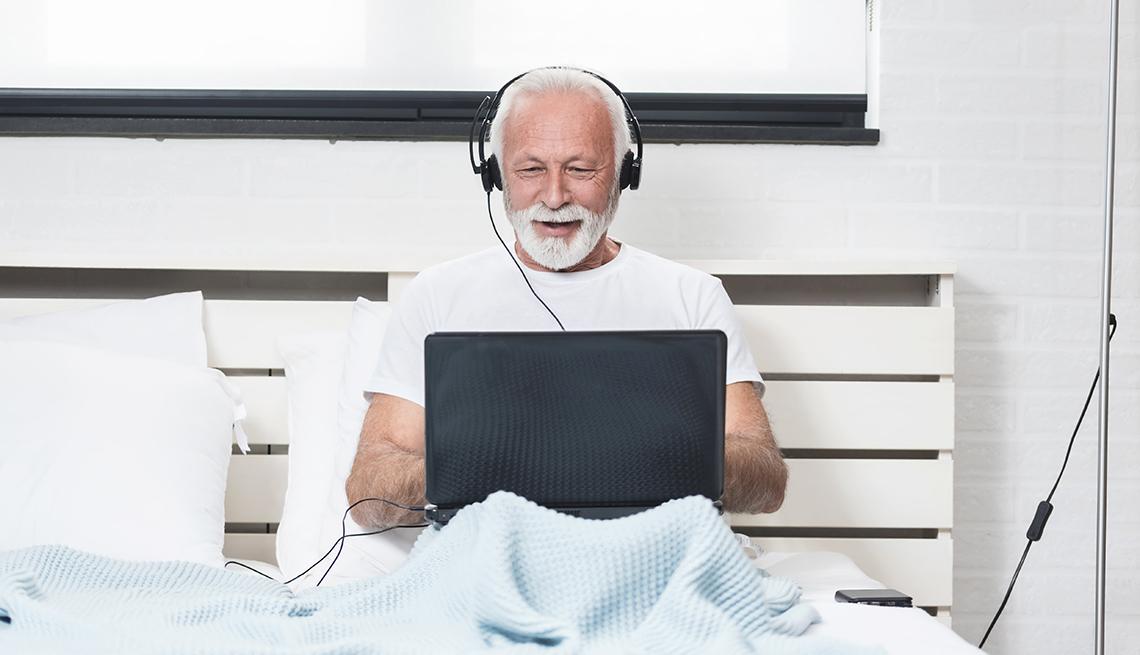 Un hombre está sentado en la cama trabajando desde su casa en su computadora portátil