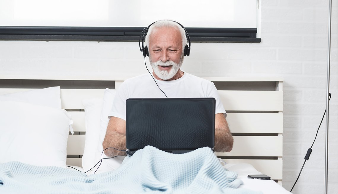 A man is sitting in bed with headphones and a computer