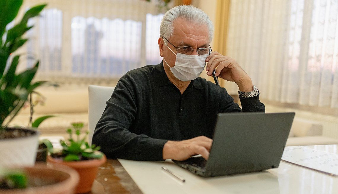 A man is talking on the phone while working on his computer