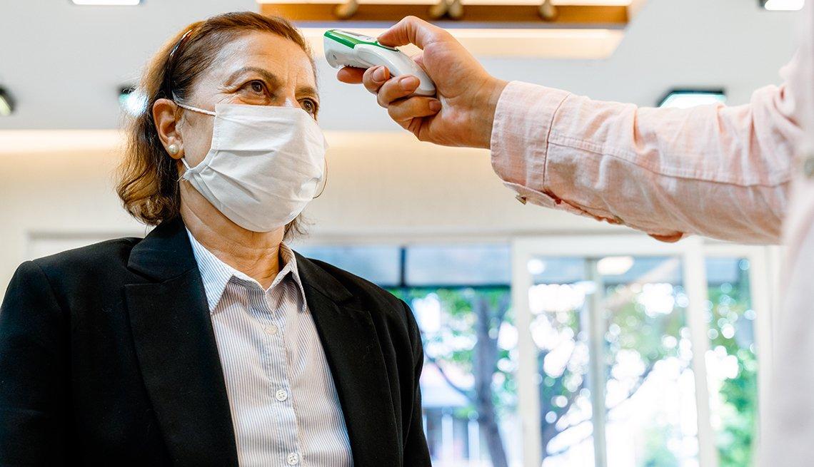 Una mujer con mascarilla a la entrada de una oficina mientras le toman la temperatura.