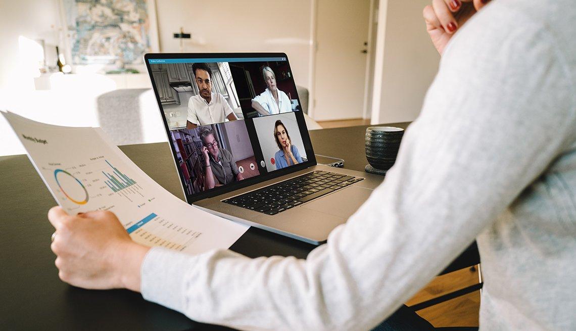 Una mujer sostiene documentos mientras está en una video conferencia desde la casa