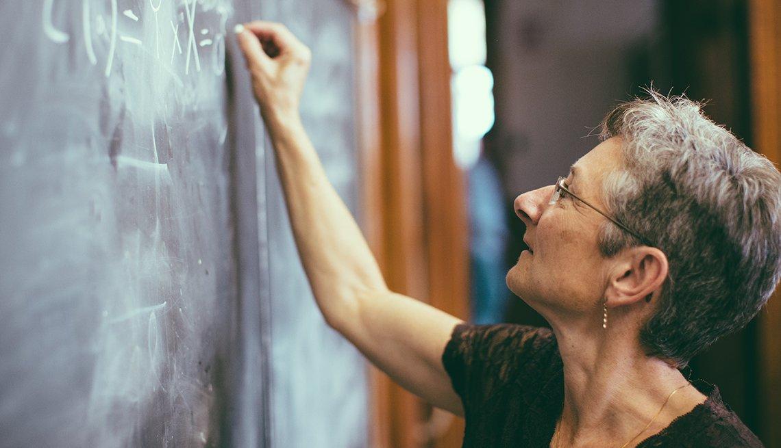 Profesora escribiendo con una tiza en un tablero.