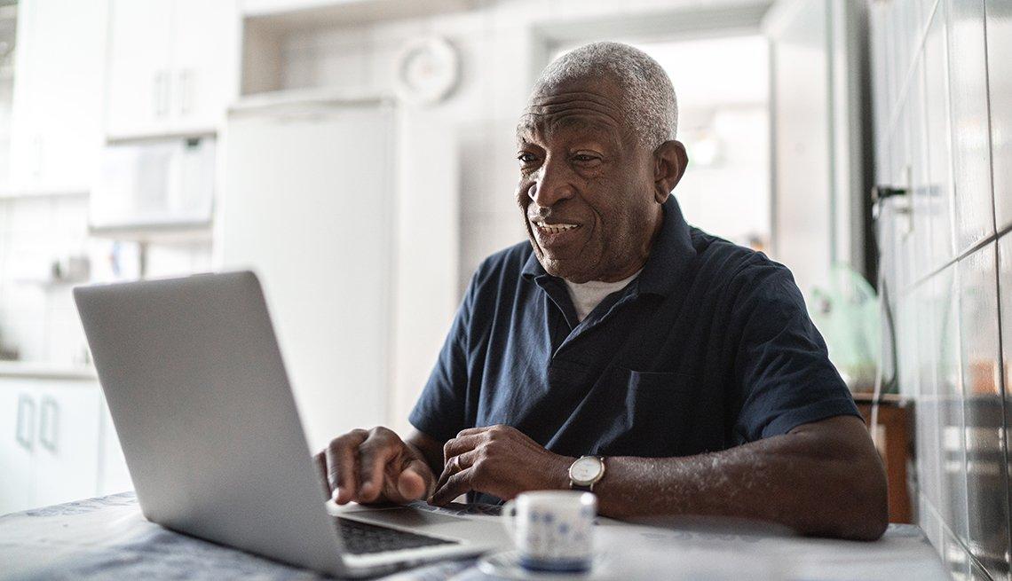 Hombre mayor sentado frente a una computadora en la cocina de su casa.