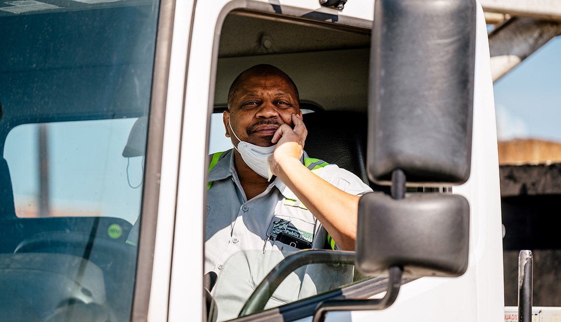 smiling man in the cab of his truck