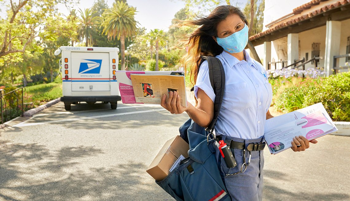 tina weber a mail carrier wearing a mask and delivering mail