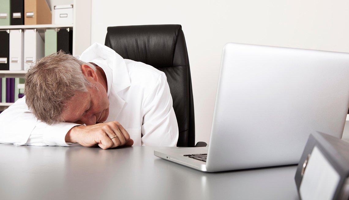 Hombre dormido sobre su escritorio y al lado de un computador