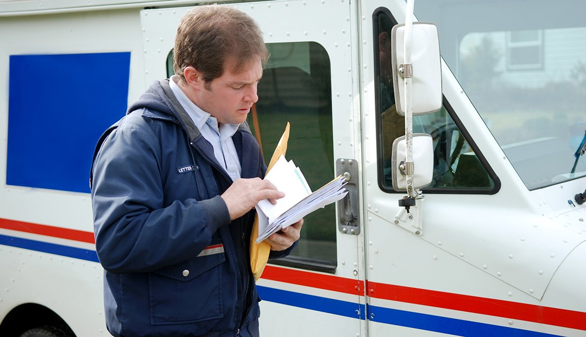 mail carrier sorting mail as he stands next to his truck