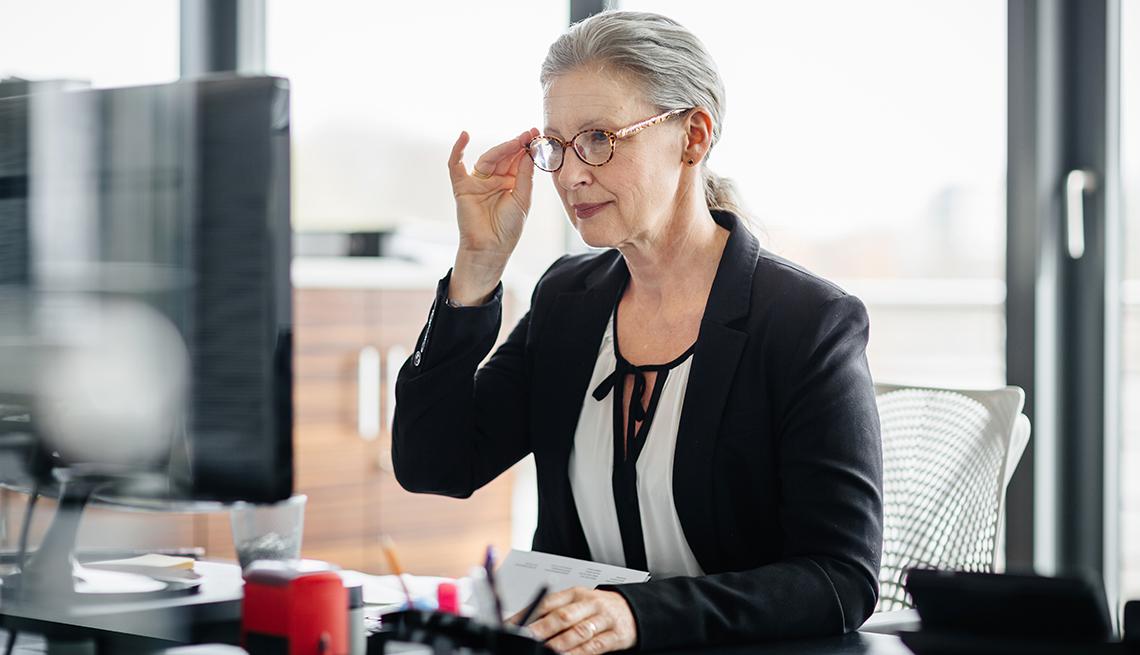 Mujer se acomoda sus anteojos mientras mira la pantalla de una computadora.