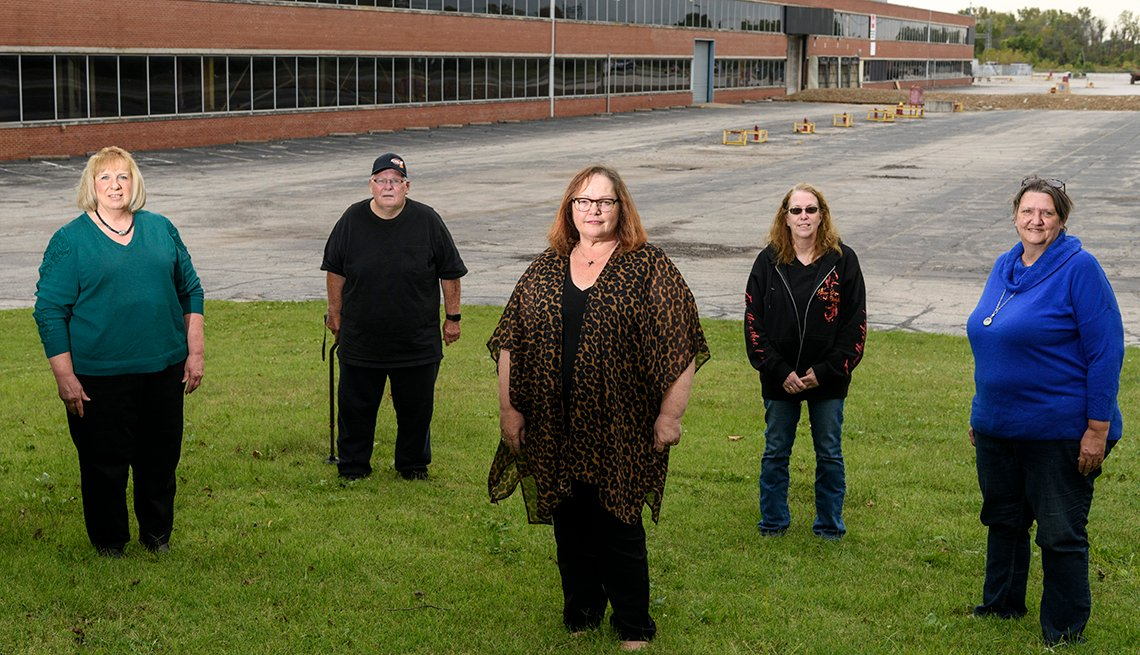 A group of people stand in front of an empty factory